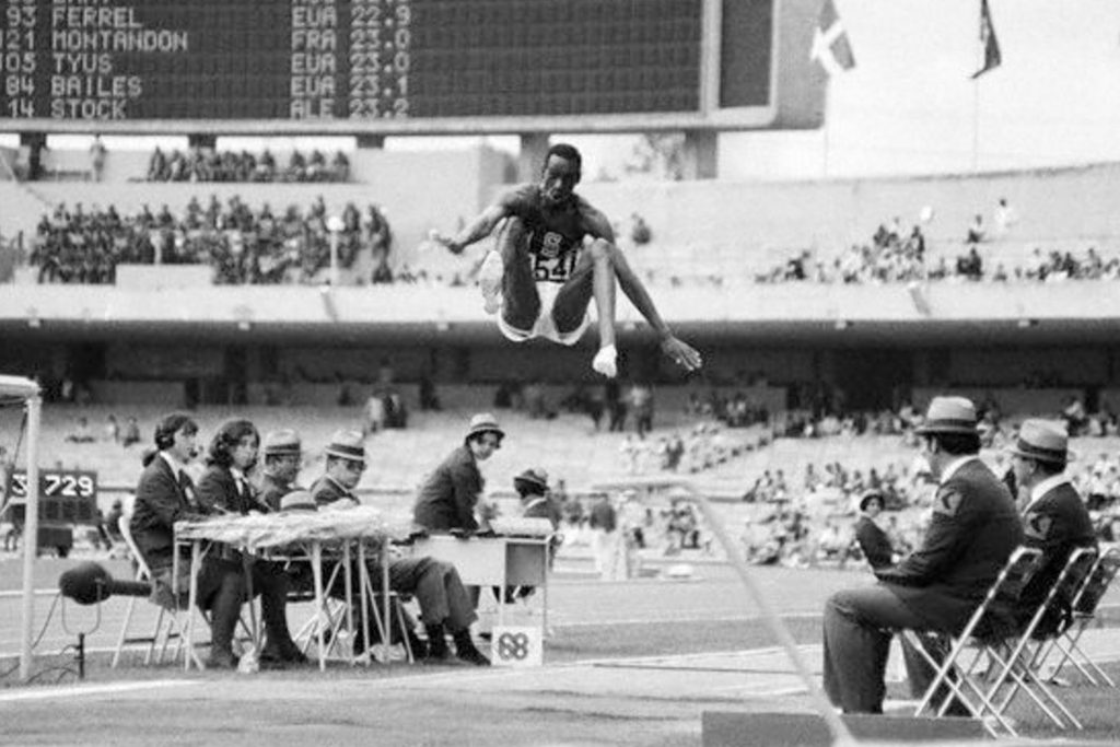 """Mladi Bob Bimon, tada 21-godišnjak sa ličnim rekordom od 8,33 metara je otvarao svojim skokom finalno takmičenje. Po vrlo tmurnom danu u Meksiko Sitiju, Bimon se na otvaranju tamičenja zaleteo koliko je brzo mogao, uhvatio dasku u milimetar i završio toliko daleko da je optička sprava, prvi put upotrebljenja na tim Olimpijskim igrama, morala da se preda, jer je bila projektovana """"samo"""" za daljine do 8,5o metara. Svetski rekord je tada bio 8,35 metara i svima je bilo jasno da je Bimon oborio Svetski rekord, ali niko nije mogao ni da predstavi koliko je njegov skok neverovatan. Sudije su počele da šire ruke, jer je svaki metar bio previše kratak da bi se izmerilo Bimonovo dostignuće."""