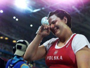 """Na Olimpijske igre 2000. godine u Sidneju, Kamila Skolimovska nije bila favorit. I pored solidnih rezultata te sezone, nije se očekivalo da jedno još uvek dete dođe do zapaženijih rezultata. Ipak, posle diskvalifikacije zbog dopinga tadašnje najbolje kladivašice sveta Mihaele Melinte, otvorila se šansa koju Skolimovska nije propustila. Sa samo 17 godina i 331 dana hicem od 71,16 metara osvojila je zlatnu medalju, postavila olimpijski rekord i postala najmlađi olimpijski šampion u bacanju kladiva u istoriji. Olimpijska titula donela joj je i veliku popularnost širom planete, mediji su pisali o novom atletskom čudu od deteta, a posebno je slavna postala u svojoj domovini, gde je zahvaljujući ostvarenom rezultatu u Sidneju dobila i orden """"Zlatni krst za zasluge"""", jedno od najvećih priznanja u Poljskoj koje sportista može da dobije."""