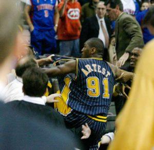 """Artest je znao da će Valas dobiti nekoliko utakmica neigranja za svoje ponašanje, pa je u jednom trenutku """"odustao"""" od dalje konfrontacije i iz samo njemu znanih razloga odlučio da legne na zapisnički sto """"Palate Oburn Hils"""". Džon Grin, navijač Pistonsa je tada plastičnom čašom dijatelne """"Koka-kole"""" pogodio Rona Artesta, koji je i dalje ležao na zapisničkom stolu. Artestu je u tom trenutku """"pao mrak"""" na oči, odmah je krenuo na nejakog navijača."""