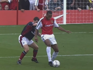 """Derbi je opravdao očekivanja, muška igra sa dosta šansi, propraćenih ovacijama sa tribina. Arsenal je bio bolji, pretio sa svih strana, najviše preko Anrija i Bergkampa, ali Junajted je imao Barteza na golu koji je bio nesavladiv, bar do 30. minuta. A onda se dogodila čarolija... Parlour je dodao jednu laganu loptu sa skoro pola terena. Anri je bio na nekih 20 metara od protivničkog gola. Imao je stamenog Denisa Irvina koji mu je disao za vratom. Ali Anri je bio igrač kakav je umeo da jednim potezom napravi razliku. Loptu je lagano podigao desnom nogom i dok su mu odmah prilazila još dva igrača """"Crvenih đavola"""", on se okrenuo i volejom poslao loptu u gornji desni ugao. Nije to bio snažan udarac, nije bilo ni traga od agresije. Samo čista elegancija i tehnika dovedena do savršenstva. Trenutak inspiracije."""